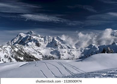 Ski tracks on fresh snow with a beautiful view of mountains in Mount Baker ski area. Fresh and heavy snow on Artish Point plato. Winter landscape in North Cascades Mountains. Washington. USA