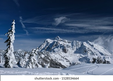 Ski tracks on fresh snow with a beautiful view of mountains in Mount Baker ski area. Fresh and heavy snow on Artist Point after snowfall. Winter landscape in North Cascades Mountains. Washington. USA