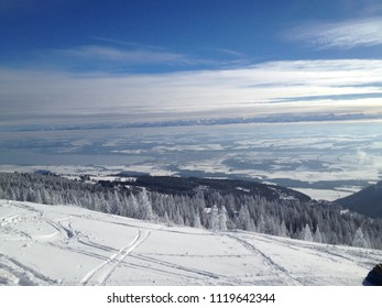 Ski tracks in the snow on a slope in Swiss Jura with a view on Lake Geneva and Pennine Alps on the other side on a blue yet cloudy cold Winter day