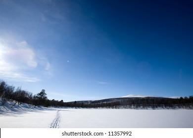 A ski trail going accross a frozen lake infront of a mountain landscape