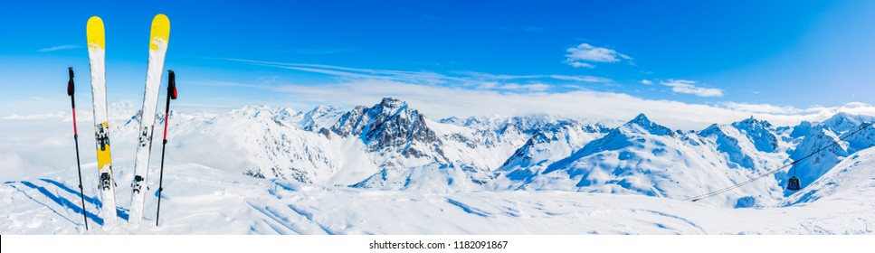Ski in winter season, mountains and ski touring equipments on the top in sunny day in France, Alps above the clouds. - Shutterstock ID 1182091867