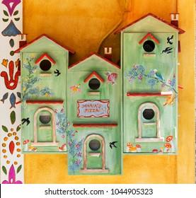 SKIATHOS, GREECE - AUGUST 18, 2017. Birds boxes outside Marias Pizza Restaurant, Skiathos Town, Greece, August 18, 2017.