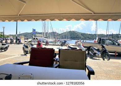 Skiathos, Greece. June 20, 2014. View from the seat of a taverna of holidaymakers and locals enjoying the new harbor quay at Skiathos town on the island of Skiathos in Greece.