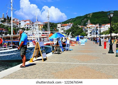 Skiathos, Greece. June 20, 2014.Holidaymakers browse the  pleasure boats and ferries in the Old port of Skiathos town on the Island of Skiathos in the Greek Islands, Greece.