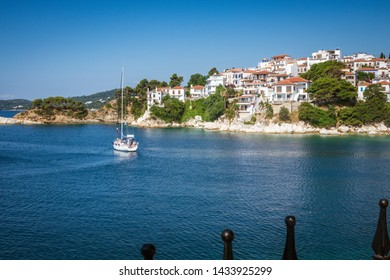 Skiathos, Greece - June 2019: Beautiful view near Skiathos island with a cruise boat leaving the old port during summer period. Amazing seascape scenery with Greek colors against a deep blue sky