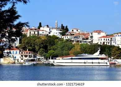 Skiathos, Greece. September 07, 2011. The old port with a a sauper yacht moored at the quay and the town on the hillside at Skiathos town on the Greek Island of Skiathos in Greece.