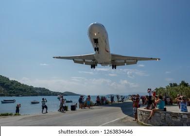 Skiathos, Greece - September 07 2018: A Fokker 70 plane landing low over tourists at Skiathos Airport