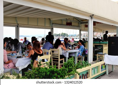 Skiathos, Greece. September 09, 2017.  Holidaymakers and tourists enjoying a meal at a seafront taverna with open sides viewing the new port at Skiathos town on the Island of Skaithos in Greece.