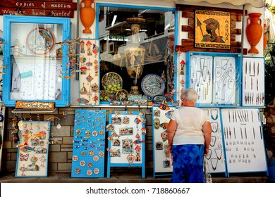 Skiathos, Greece. September 13, 2017.  A senior holidaymaker browzing the shop window of a Greek arts shop in the back streets of Skiathos town on Skiathos Island in Greece.