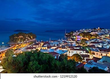 SKIATHOS ISLAND, NORTHERN SPORADES, GREECE- June 23, 2018. Night view of Skiathos town from the clock tower of Agios Nikolaos church.