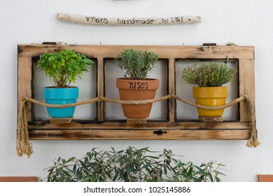 Skiathos/Greece-Sep-14-2017: Traditional colorful pots with plants on wall in wooden frame in Greece, in Skiathos town