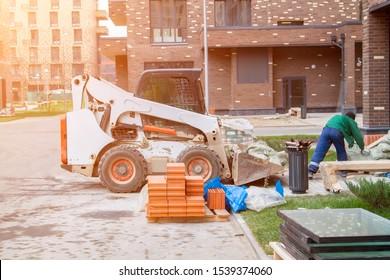 Skid loader is in yard of new multi storey building with garbage bags in bucket