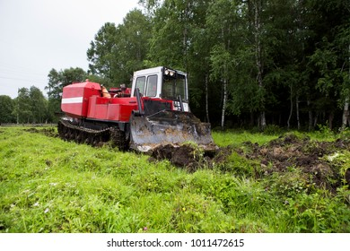The skid tractor opens the fire-prevention strip. The skidder tractor cuts with a knife and sends the top layer of soil with the grass to the heap. Prevention of fires in the forest.