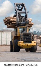 Skidder hauling logs at sawmill.