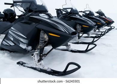 Skidoos in a row at a glacier