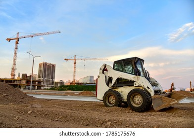 Skid-steer loader working at construction site. Сompact construction equipment for work in limited conditions.