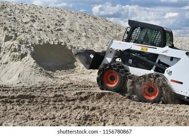 skid-steer loader working with sand
