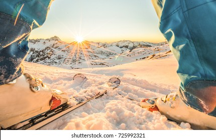 Skier athlete standing in front of wonderful sunset in ski resort - Winter extreme sport concept with person on top of the mountain ready to ride down - Focus on intersection skis
