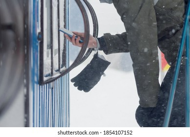 Skier is buying the ski pass card in the cash box close up.