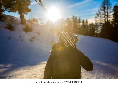 Skier carries skis walking home at sunset after day of skiing