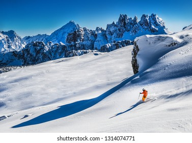 Skier in deep snow makes a snow wave behind him. Free rider going fast in fresh snowy slope high in winter mountains.