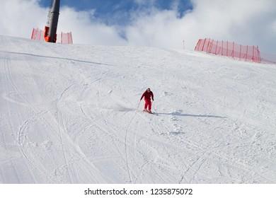 Skier descend on snowy sunlight ski slope at sun winter day. Greater Caucasus Mountains, Shahdagh, Azerbaijan.