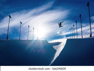 Skier doing an inverted trick in winter snow halfpipe