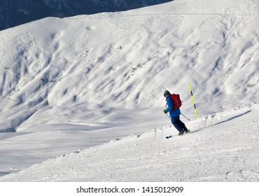 Skier downhill on snowy ski slope in cold sunny evening. Caucasus Mountains, Georgia, region Gudauri at winter.