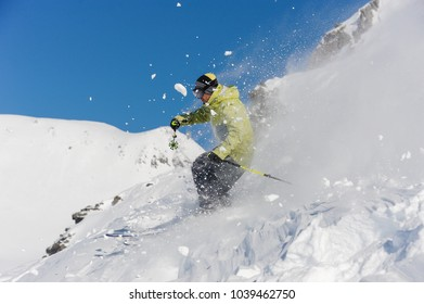 Skier dressed in yellow and grey sportswear running down the slope on the background of Gudauri, Georgia