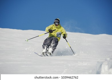 Skier dressed in yellow and grey sportswear running down the mountain slope in beautiful resort Gudauri, Georgia