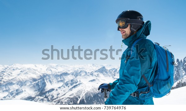 Skier enjoying the stunning view before free ride skiing. Happy man contemplate winter mountain landscape with copy space. Free man with ski mask and helmet enjoying holiday in snow mountain.