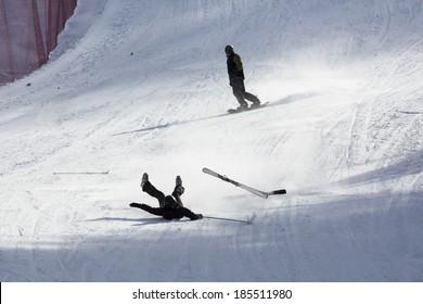 skier falling down white on mountain slope