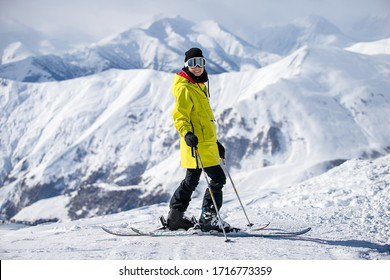 A skier in a fashionable yellow jacket is skiing against the backdrop of the Caucasus Mountains