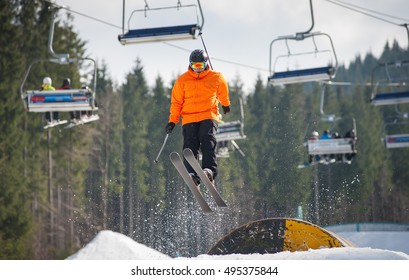 Skier flying over a hurdle in winter day with forest of firs and ski lifts in background at a winter resort. Bukovel, Ukraine