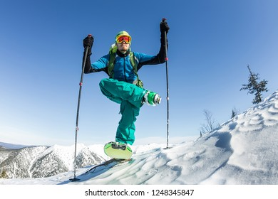 Skier freerider doing yoga skiing in snowy mountains