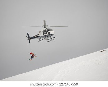 Skier freerider jumps from helicopter heliski on a snowy mountain