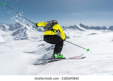 A skier in full sports equipment jumps into the abyss from the top of the glacier against the background of the blue sky and the Caucasian snow-capped mountains. View from the back. Elbrus region