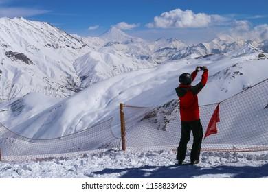 Skier girl taking selfie at the ski resort peak. Damavand in background. Dizin ski resort. North Tehran.