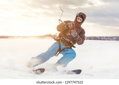 The skier goes on the snow field with kite in winter
