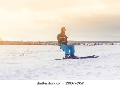 The skier goes on the snow field with kyte in winter