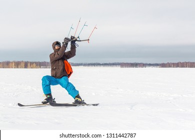 The skier goes on the snow field with kyte