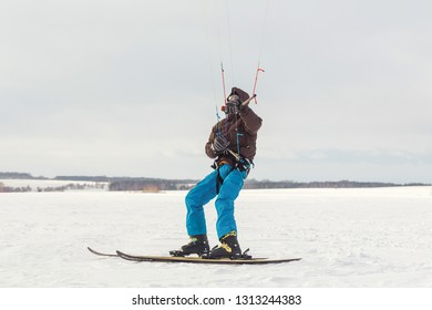 The skier goes on the snow field with kite
