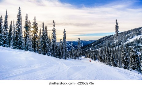 Skier going down the ski slopes surrounding the alpine village of Sun Peaks in the Shuswap Highlands of central British Columbia, Canada on a late afternoon