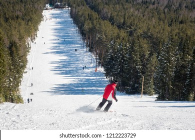 Skier going down the slope. ski trail for skiing and skateboarding. active rest and sport. shot from the top of the slope. people skiing downhill. ski resort