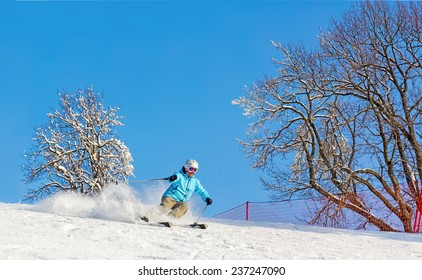 Skier at high speed on piste in soft snow on a sunny day on a background of trees and cloudless blue sky