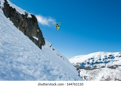 Skier invested in the air. Leaping over the stones, powder snow, off piste. Making a turn in the air.