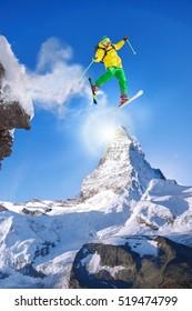 Skier jumping against Matterhorn peak in Switzerland.