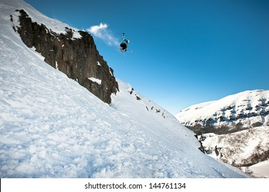 Skier jumping on the rocks, off-piste.