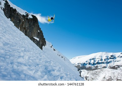 Skier jumping on the stones, powder snow, off piste. Making a turn in the air.