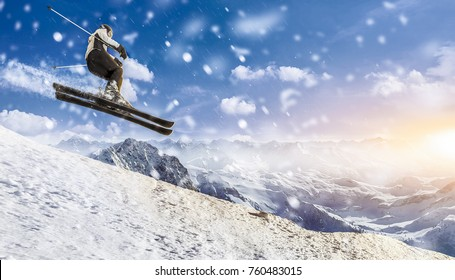 skier jumps downhill through the air with high speed. she takes a snow spray with her while she enjoys the beautiful mountain panoramic landscape. snow is falling and sun is shining.